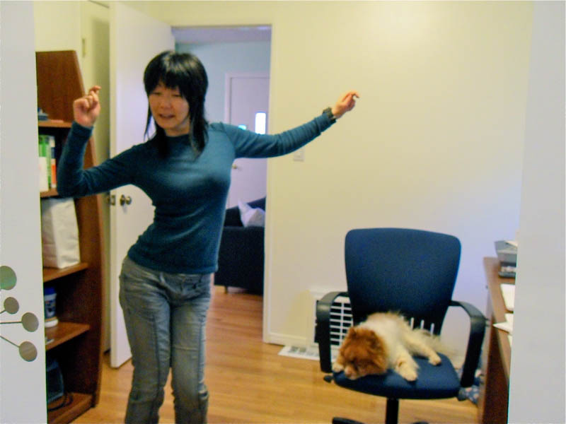 photo of Jennifer Moon dancing in her office while Mr. Snuggles sleeps on her chair